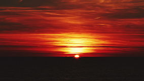 Beautiful red sunset over the sea with red clouds, the sun disappears behind the horizon. stock video
