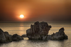 Beautiful red sunset with rock on the sea. Italy Stock Image
