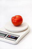 Beautiful red tomato on a white kitchen scale Stock Image