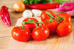 Beautiful red tomatoes and vegetables in the background. Healthy vegetables ready to be cooked Stock Photography