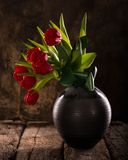 Beautiful red tulips in black vase Royalty Free Stock Photo