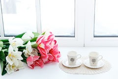 Beautiful red tulips in vase and two cups on a window sill. Royalty Free Stock Photos