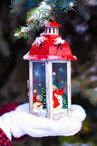 Beautiful red vintage Christmas lantern on warm mittens Royalty Free Stock Images