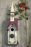 Beautiful red and white church birdhouse on rustic fence Stock Photo