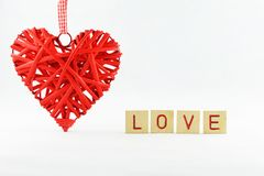 beautiful red wicker heart with a white background with letters inscription love royalty free stock images