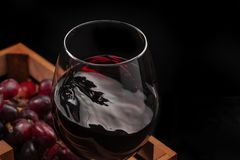 Beautiful red wine splash in a glass goblet in a wooden box with grapes, black background.  stock image