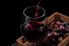 Beautiful red wine splash in a glass goblet in a wooden box with grapes, black background.  royalty free stock images