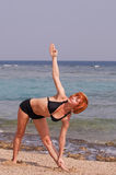 Beautiful red woman exercising at the beach Royalty Free Stock Photos