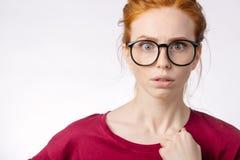 Beautiful redhair girl wearing glasses shocking with something Royalty Free Stock Photos