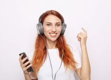 Beautiful redhair woman in headphones listening to music stock photos