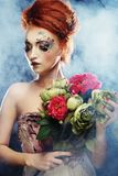 Beautiful redhair woman holding flowers. Young beautiful redhair woman with bright creative visage holding flowers royalty free stock images