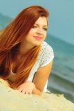 Beautiful redhaired girl on beach, portrait. Holidays, vacation travel and freedom concept. Beautiful redhaired happy girl on beach, portrait Stock Photo