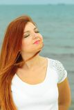 Beautiful redhaired girl on beach, portrait. Holidays, vacation travel and freedom concept. Beautiful redhaired happy girl on beach, portrait Royalty Free Stock Photos