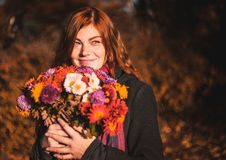 Beautiful redhaired girl with a flowers. stock photos