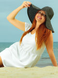 Beautiful redhaired girl in hat on beach, portrait. Holidays, vacation travel and freedom concept. Beautiful redhaired happy girl in hat on beach Stock Photos