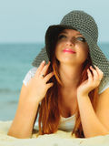 Beautiful redhaired girl in hat on beach, portrait. Holidays, vacation travel and freedom concept. Beautiful redhaired happy girl in hat on beach Stock Image
