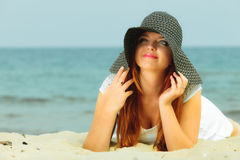 Beautiful redhaired girl in hat on beach, portrait. Holidays, vacation travel and freedom concept. Beautiful redhaired happy girl in hat on beach Royalty Free Stock Photos