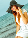 Beautiful redhaired girl in hat on beach, portrait. Holidays, vacation travel and freedom concept. Beautiful redhaired happy girl in hat on beach Stock Photo