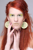 Beautiful redhaired girl with lemon slices in ears Stock Image
