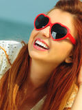 Beautiful redhaired girl in sunglasses on beach, portrait Stock Images