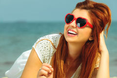 Beautiful redhaired girl in sunglasses on beach, portrait Stock Photo