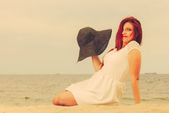 Beautiful redhaired happy girl in black hat on beach. Royalty Free Stock Image