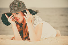 Beautiful redhaired happy girl in black hat on beach. Stock Images