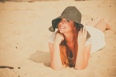 Beautiful redhaired happy girl in black hat on beach. Royalty Free Stock Photo