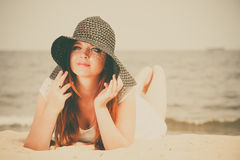 Beautiful redhaired happy girl in black hat on beach. Stock Photos