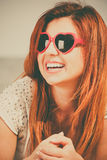 Beautiful redhaired happy girl in heart shaped sunglasses on beach. Royalty Free Stock Image