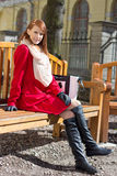 Beautiful redhaired woman crossing sitting on the bench Royalty Free Stock Image
