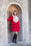 Beautiful redhaired woman posing in front of the old door Stock Image