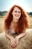 Beautiful redhead on the bale of straw Stock Photo