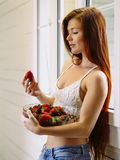 Beautiful redhead with bowl of strawberries royalty free stock images