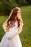 Beautiful redhead Bride in fantastic wedding dress in blooming garden. Portrait in sunset light. Pretty young caucasian redhead girl walks in a garden and Royalty Free Stock Image