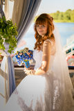 Beautiful redhead bride holding bouquet on summer terrace Stock Photography