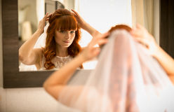 Beautiful redhead bride looking in mirror and attaching veil Stock Image