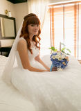 Beautiful redhead bride sitting on bed with bouquet Royalty Free Stock Photography