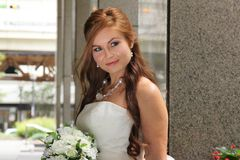 Beautiful redhead bride smiles, looking off camera. Beautiful caucasian redhead smiles with a bouquet of flowers, wearing a white strapless dress, while her long Stock Photography