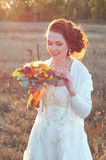 Beautiful redhead bride in white dress holding autumn bouquet Royalty Free Stock Photo