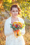 Beautiful redhead bride in white dress holding autumn bouquet Stock Photos