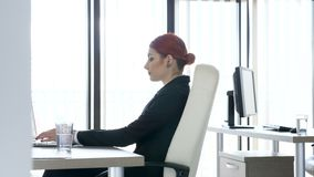 Beautiful redhead businesswoman at her desk in the office typing on the laptop then looks at the camera and smiles. Revealing shot of beautiful redhead stock video footage