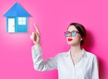 Beautiful redhead businesswoman pointing on house. On pink background royalty free stock photo