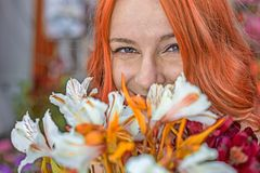 Beautiful redhead Caucasian girl smelling colorful flowers in the garden royalty free stock photo