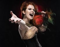 Beautiful redhead cosplayer girl wearing Victorian-style steampunk dress screams, pulls her hair by her hand and outstretching her. Hand. Red and black royalty free stock images