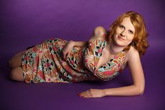Redhead in a dress on a violet background. Beautiful redhead in dress lying in studio on a violet background, fashion photo Stock Photo
