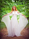 Beautiful redhead elf woman wearing white dress in a garden Stock Photography