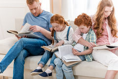 Beautiful redhead family sitting on sofa and reading books together. Big family portrait royalty free stock photo