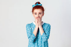 Beautiful redhead female in blue dress doesn`t want to spread rumors or some confidential information. Portrait of serious young ginger. Caucasian girl covering Royalty Free Stock Images