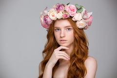Beautiful redhead female with curly red hair in flower wreath. Beautiful redhead young female with curly red hair in flower wreath over grey background Stock Image